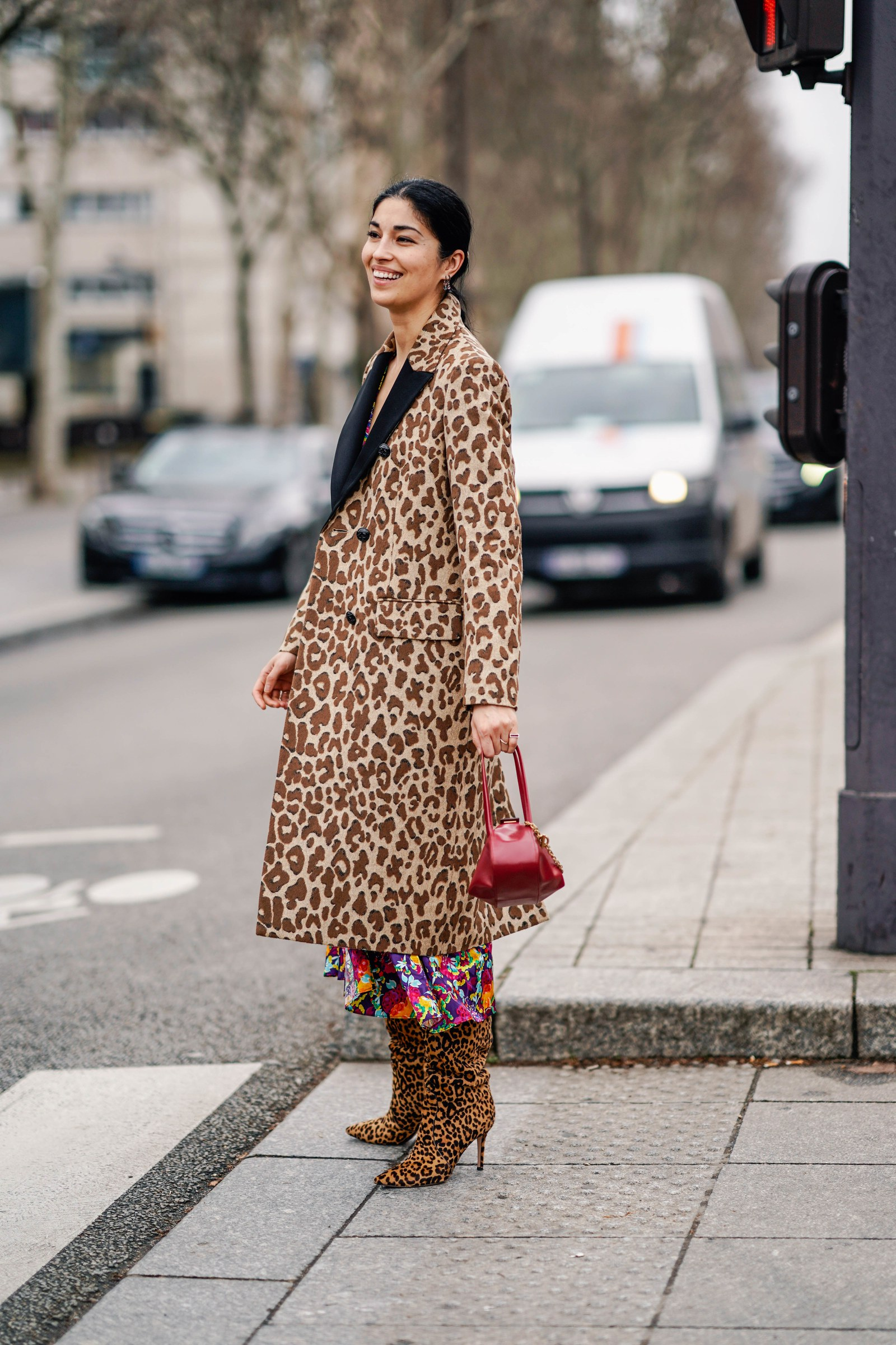 Caroline Issa wears a Dolce Gabbana brown leopard print coat with black lapels a colorful floral print flowing dress a...