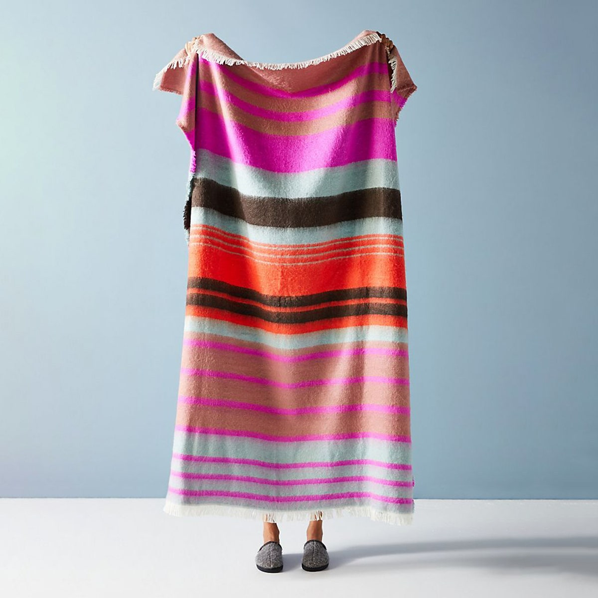 person holding bright pink orange green and blue stripe blanket throw in front of blue wall